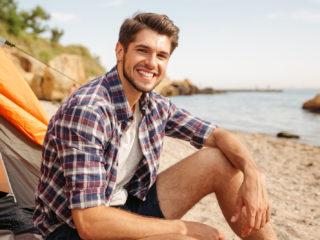 un homme souriant assis sur la plage