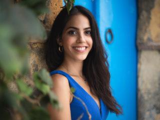 femme heureuse en robe bleue se tenant près d'une porte