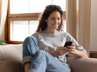 une femme souriante est assise sur le canapé et les touches du téléphone
