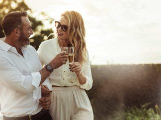 un homme et une femme se tiennent debout et trinquent avec du vin