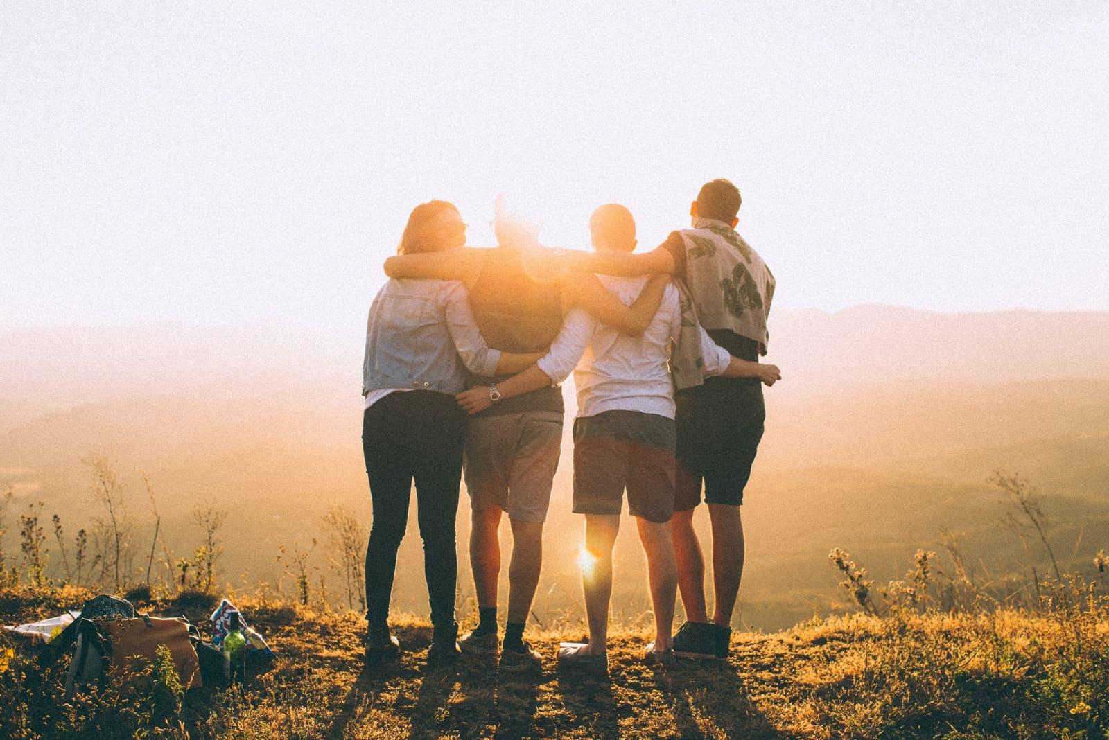 quatre amis s'embrassant en plein air