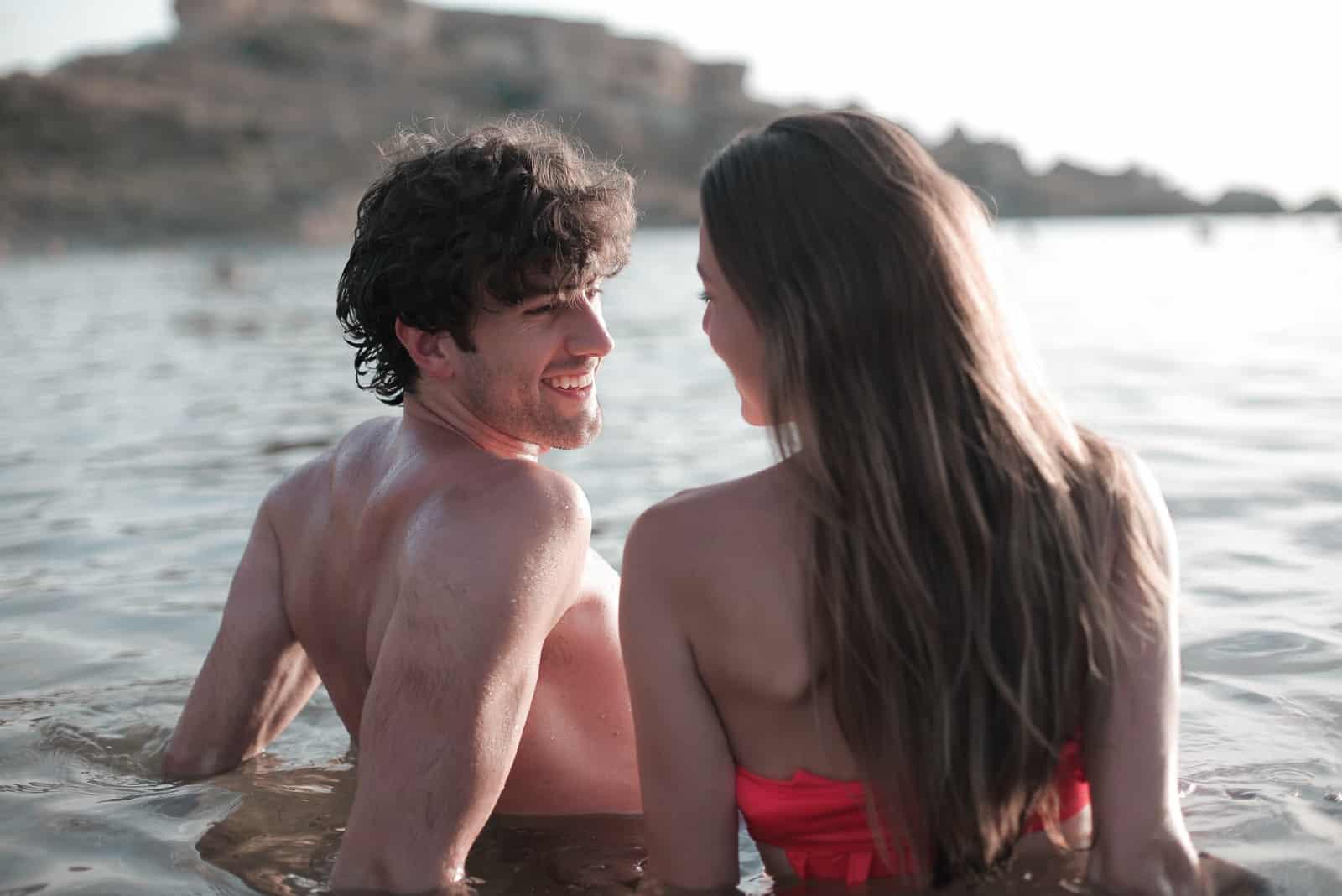 homme et femme souriant assis dans l'eau
