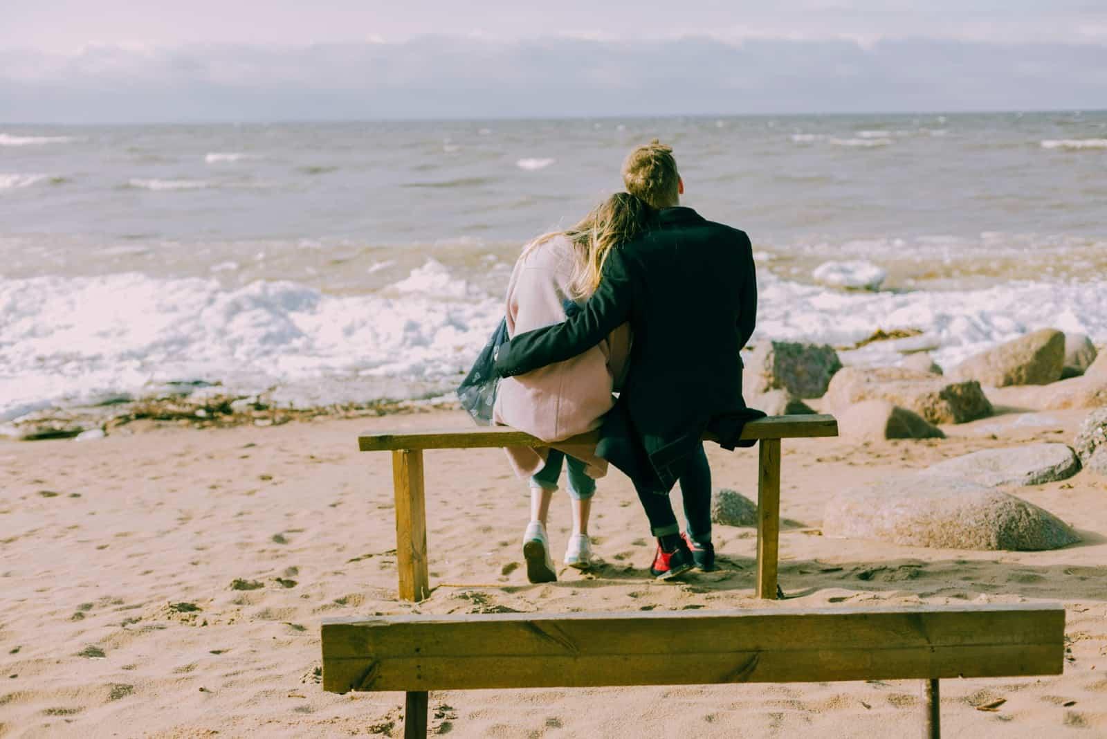 homme et femme s'embrassant assis sur un banc
