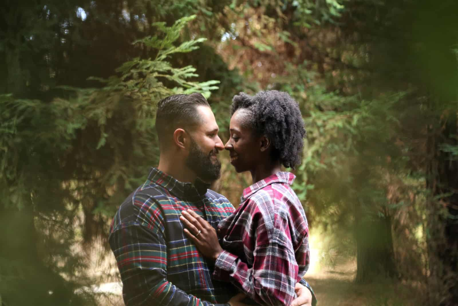 homme et femme s'embrassant dans une forêt