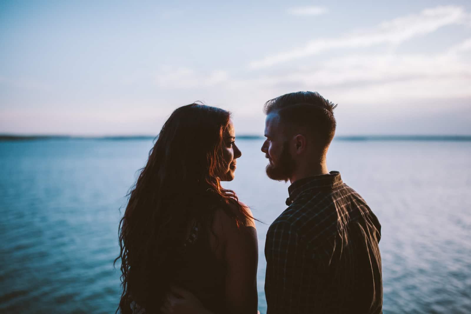 homme et femme établissant un contact visuel près de l'eau