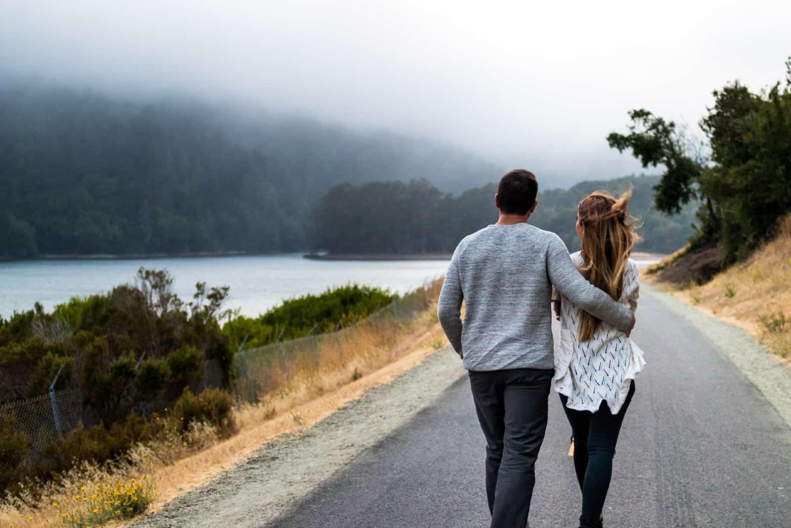 homme et femme marchant sur la route