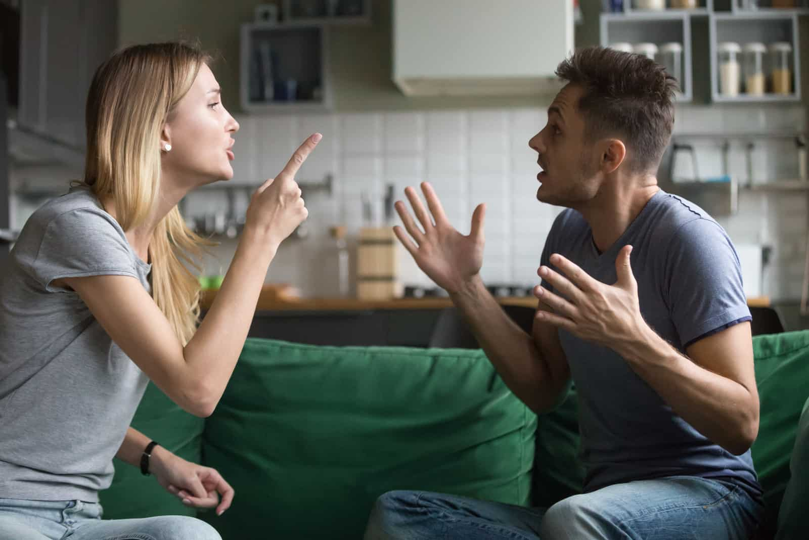 homme et femme se disputant assis sur un canapé