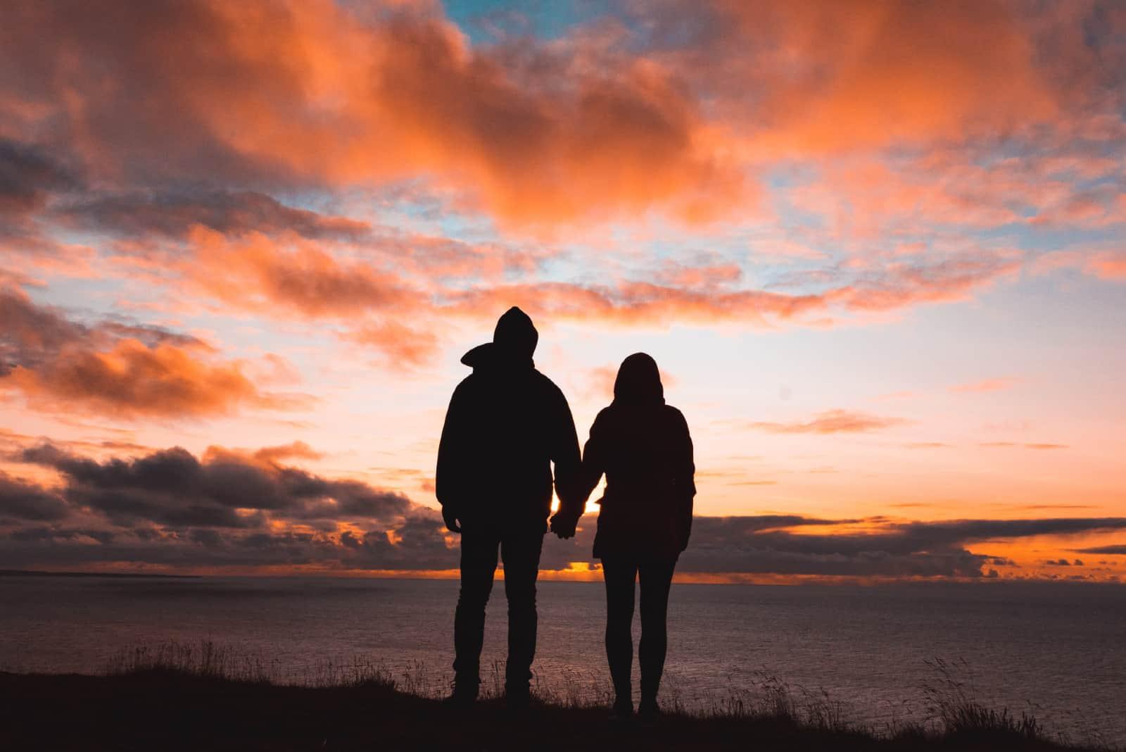 un homme et une femme se tenant la main en se tenant sur une falaise