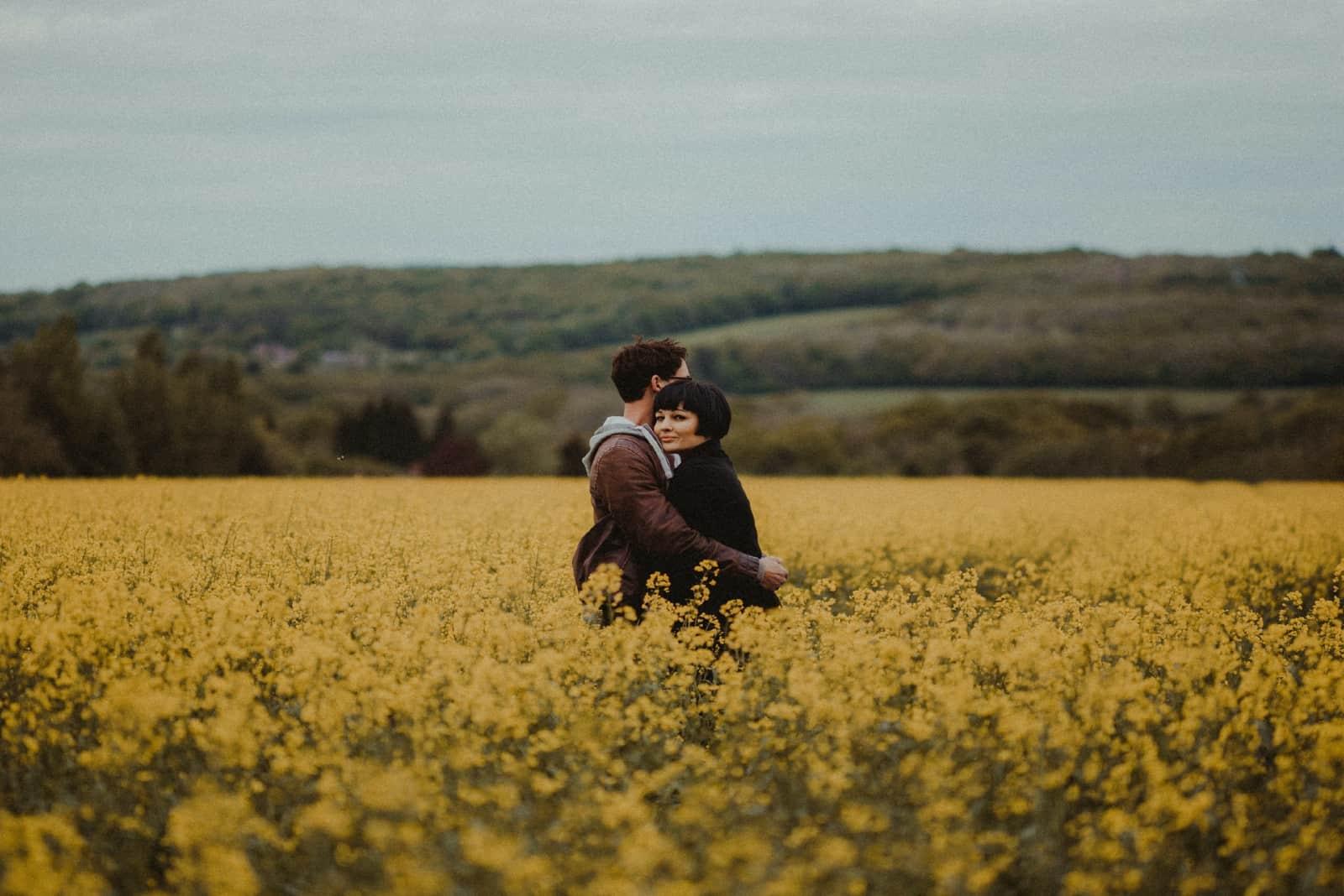 homme et femme s'embrassant en se tenant dans un champ