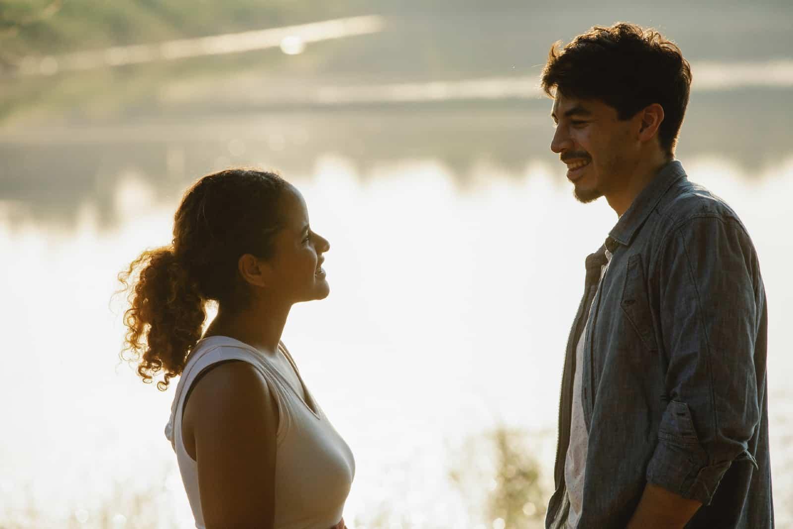 Un homme et une femme sourient en se tenant près de l'eau