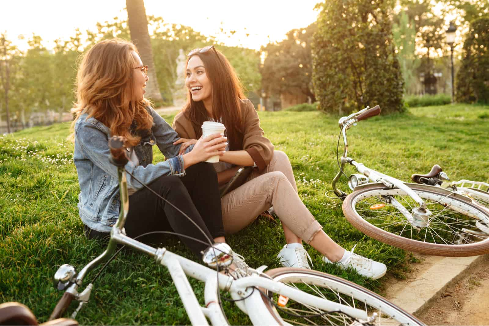 deux amis sont assis sur l'herbe dans le parc et parlent