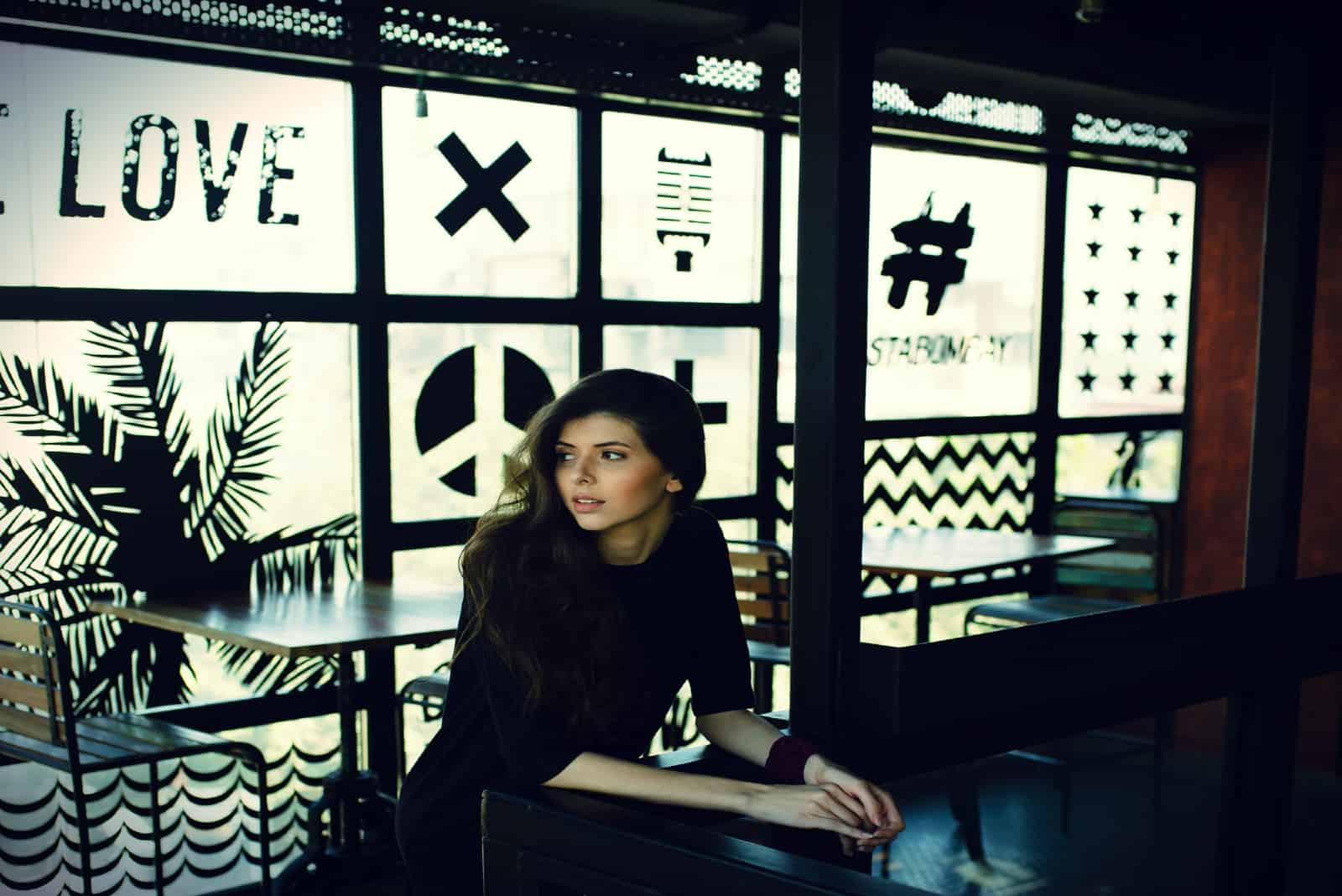 femme pensive en haut noir appuyée sur une table