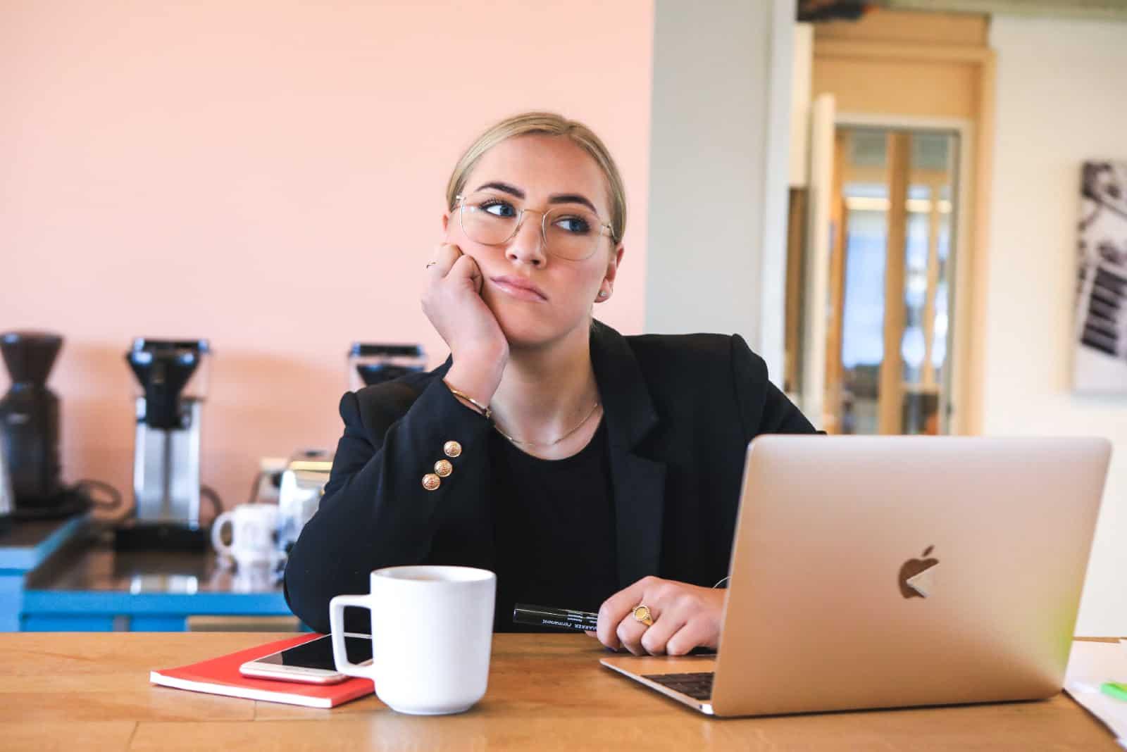 femme ennuyée avec des lunettes appuyée sur une table
