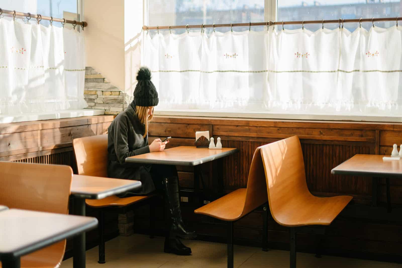 femme utilisant un smartphone alors qu'elle est assise à une table