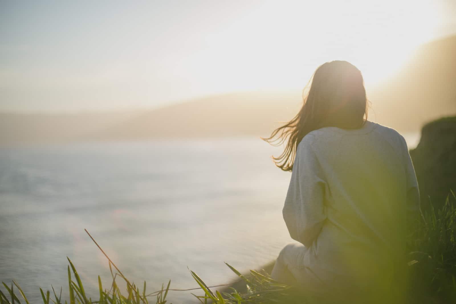 femme en sweat-shirt gris assise près de la mer
