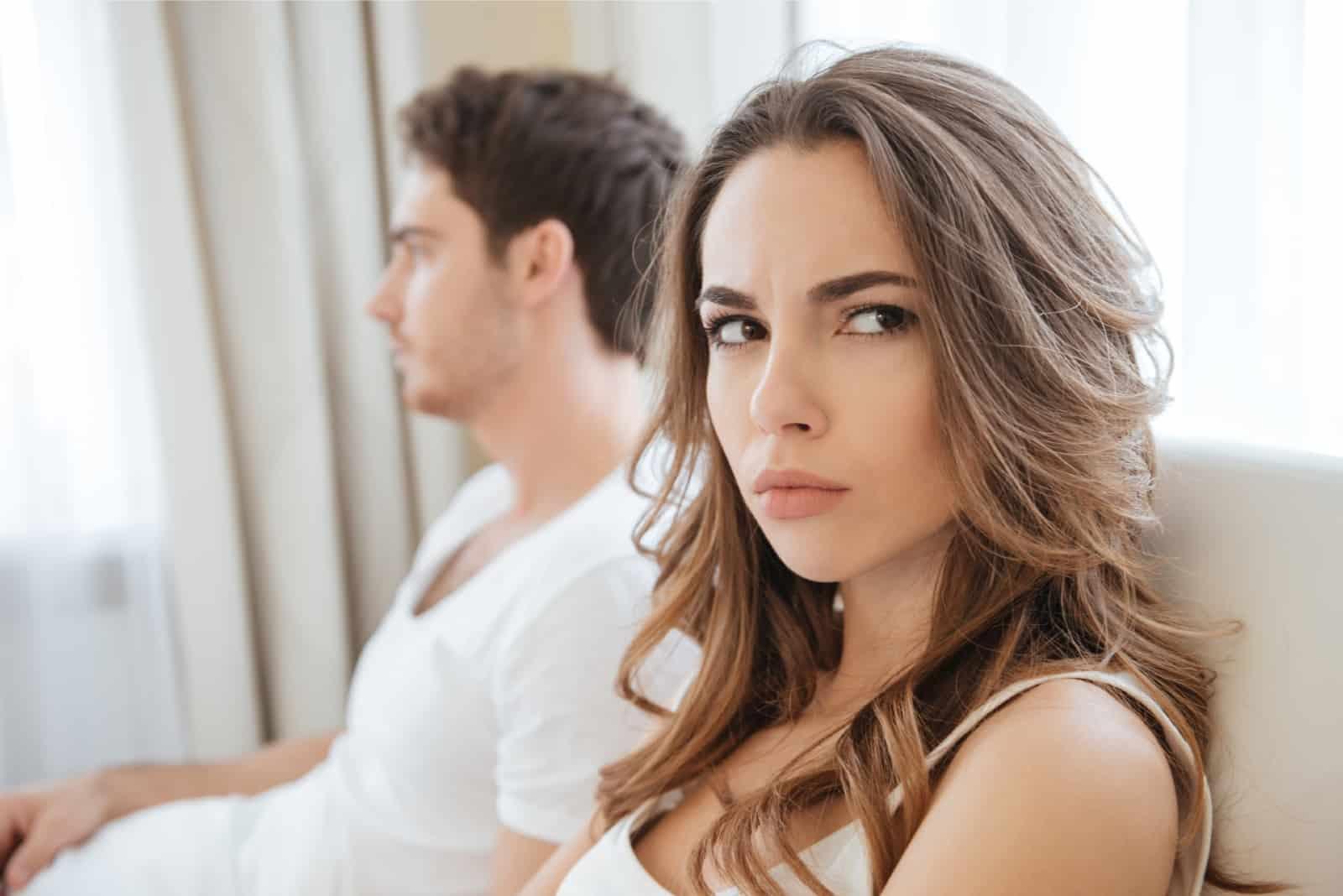 femme en colère avec un haut blanc assise près d'un homme