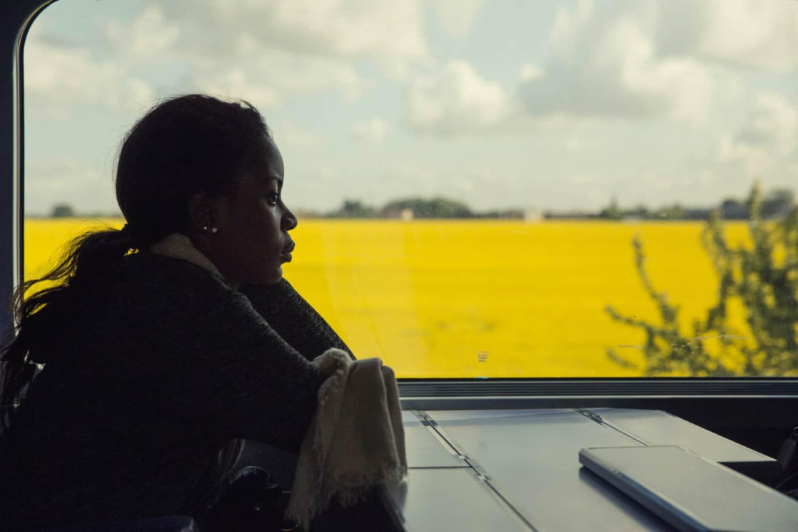 femme pensive en chandail noir assise près d'une fenêtre