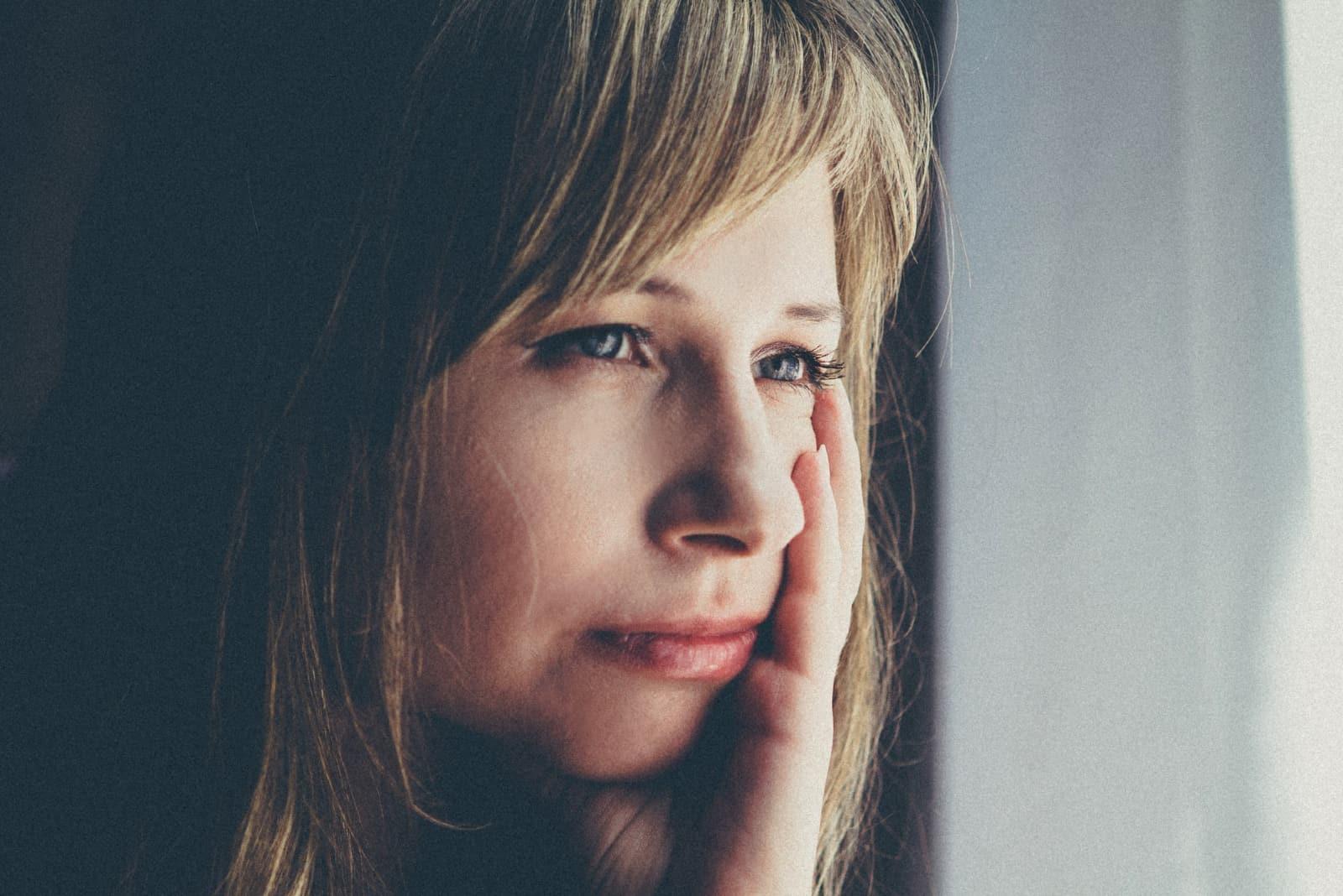 femme pensive assise près d'une fenêtre