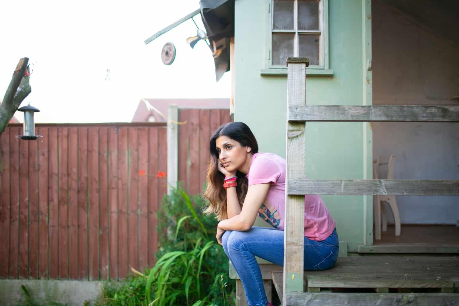 femme en t-shirt rose assise près d'une maison