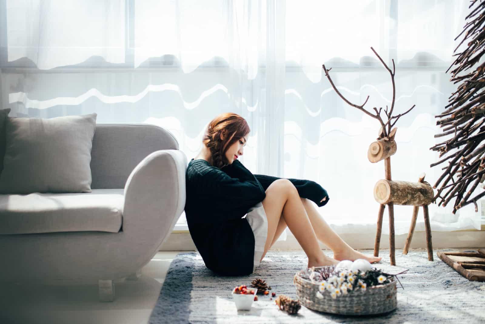 femme triste assise sur le sol près d'un canapé