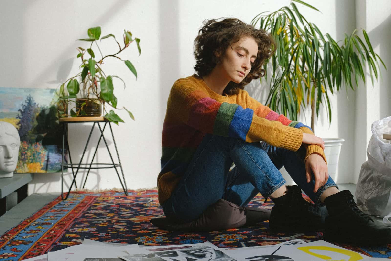 femme triste assise sur le sol près d'une usine