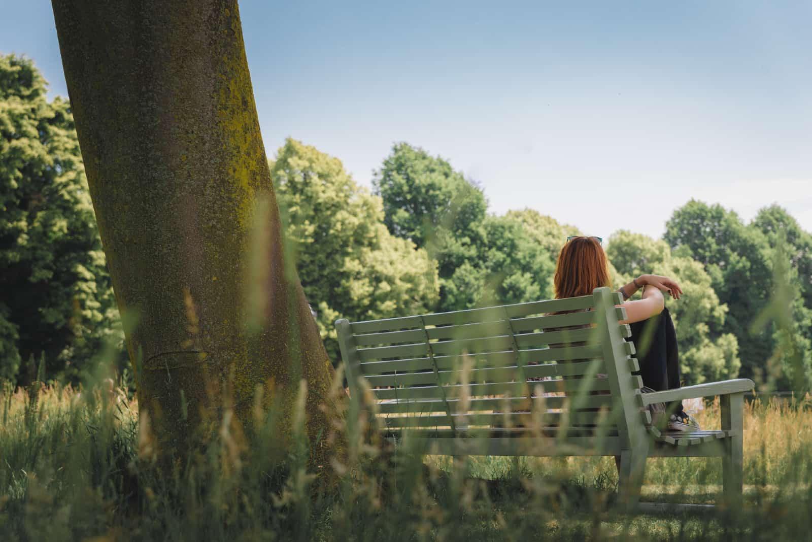 femme assise sur un banc près d'un arbre