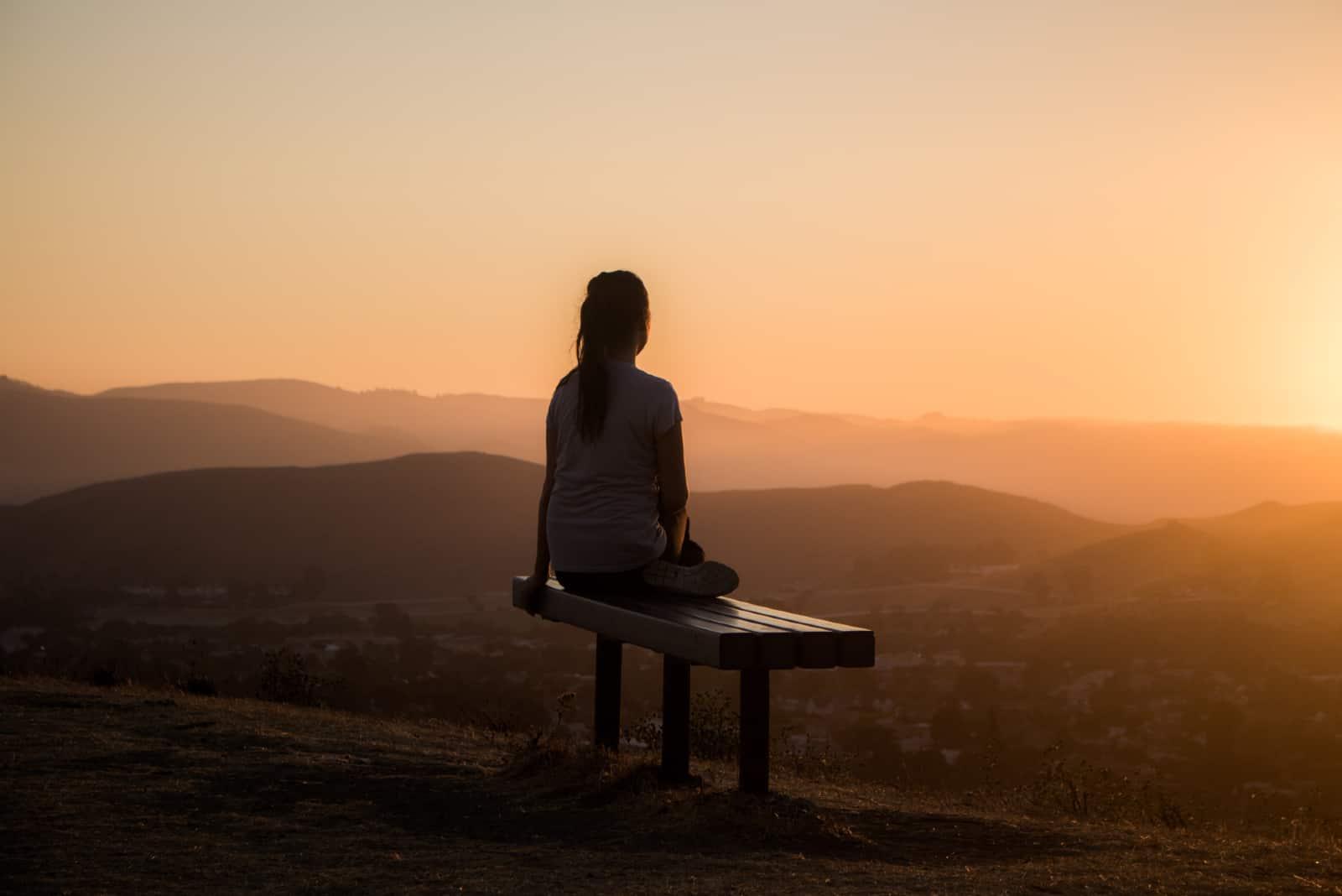 femme assise sur un banc regardant la montagne