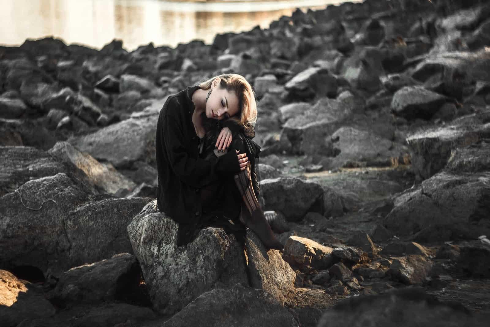 femme triste en robe noire assise sur un rocher