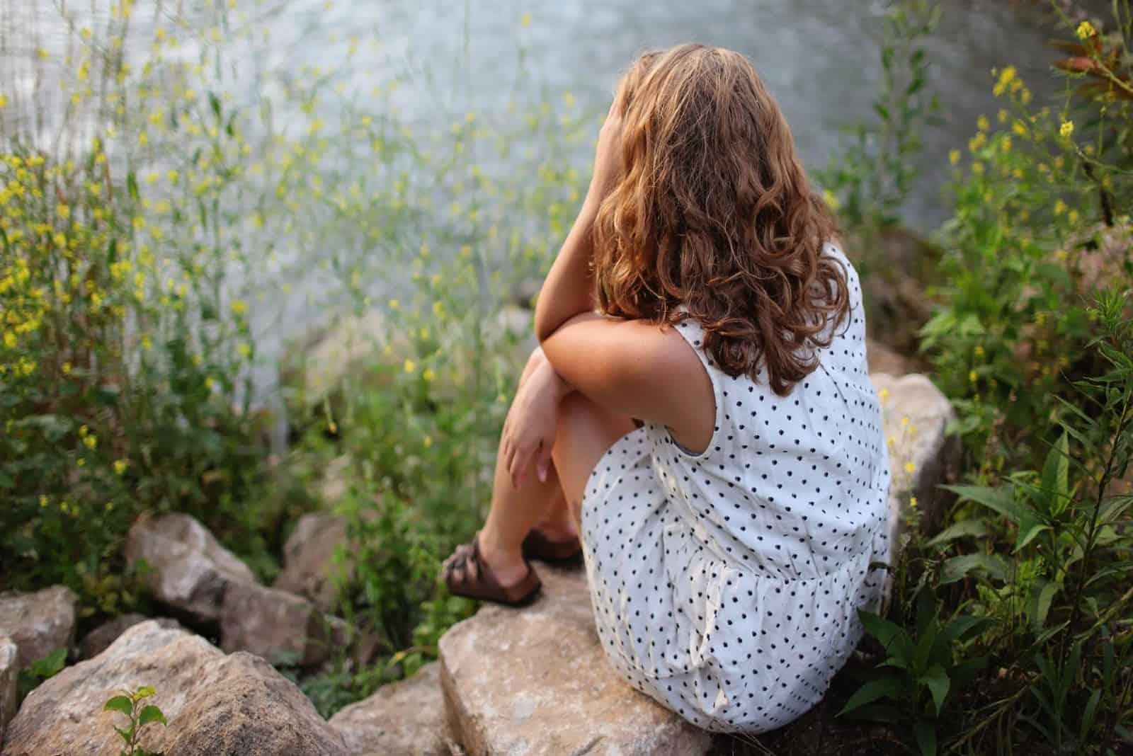 femme en robe blanche à pois assise sur un rocher