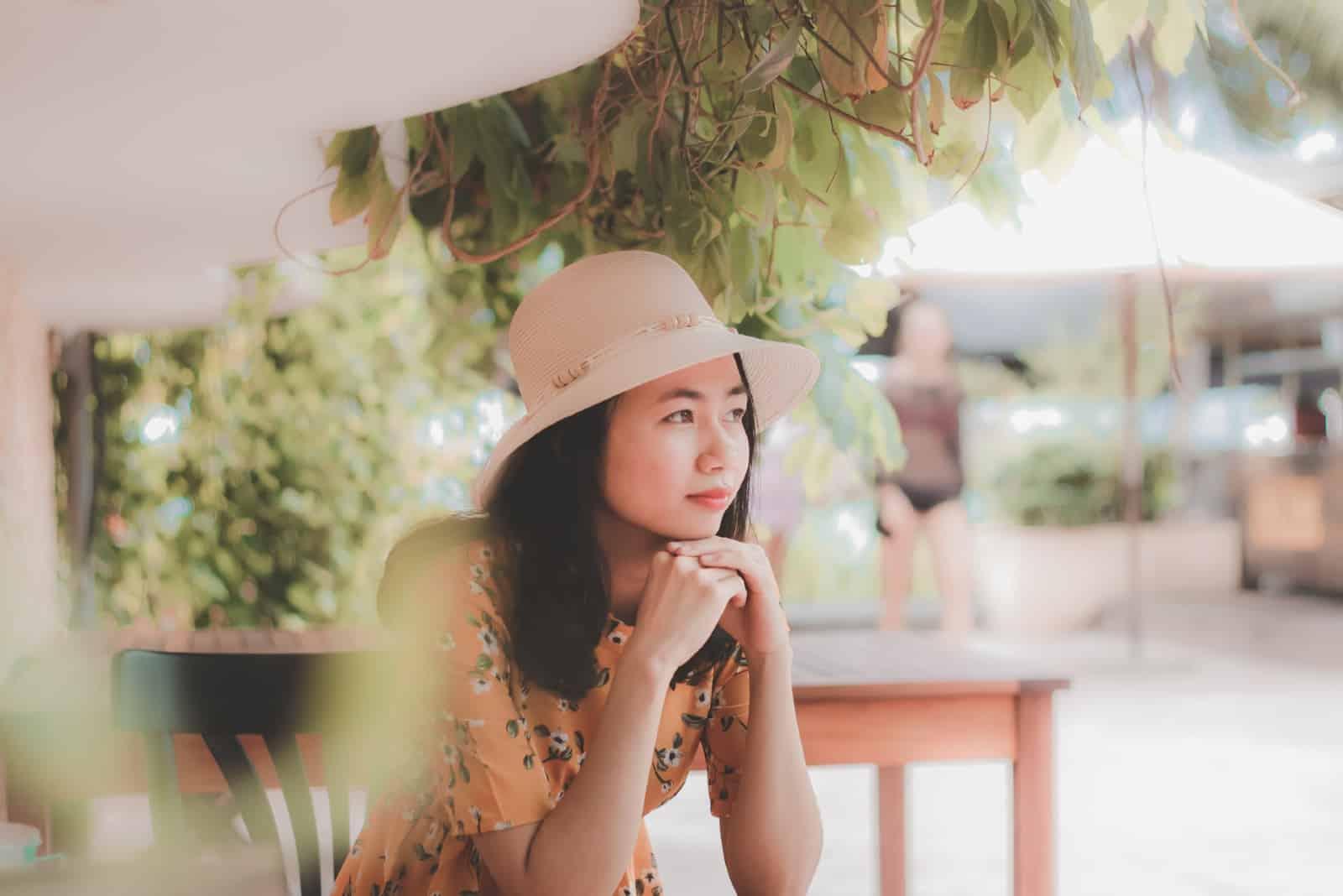 femme pensive avec un chapeau assise sur une chaise