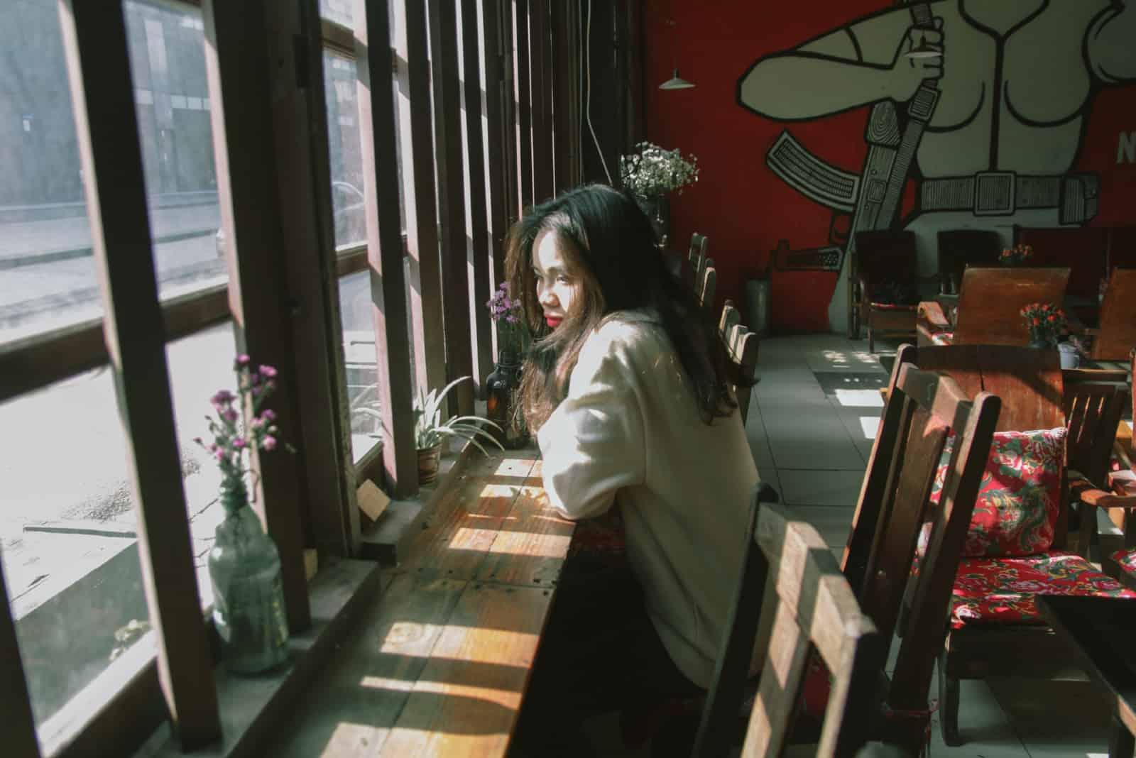 femme triste assise sur une chaise près d'une fenêtre