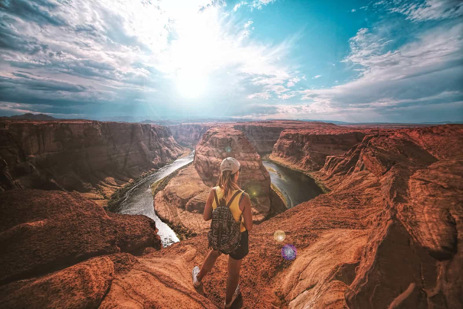 femme avec un sac à dos au sommet d'un canyon