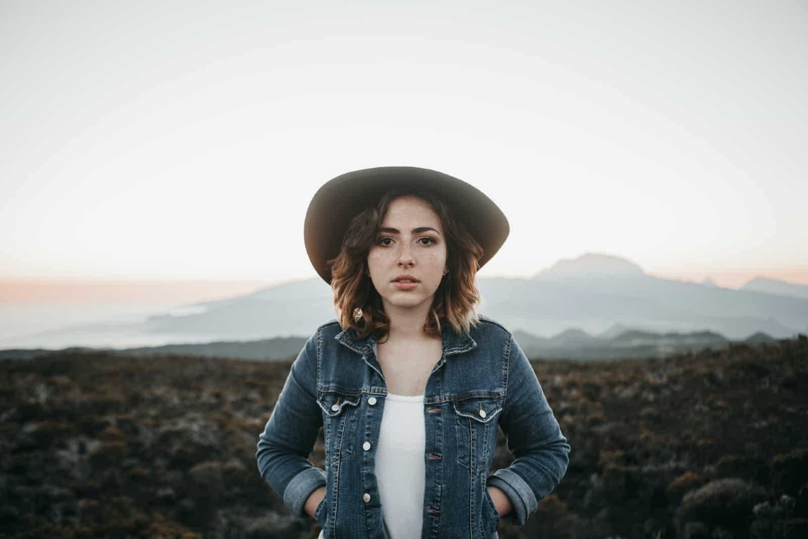 femme avec une veste en jean debout dans un champ