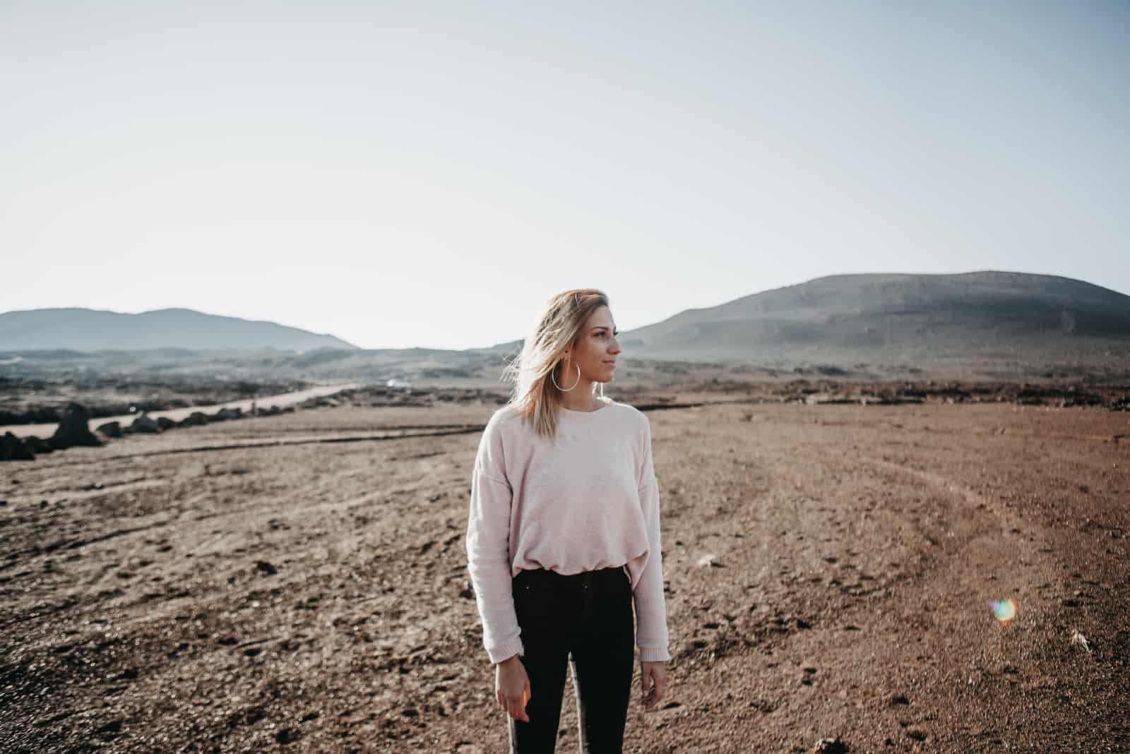 femme blonde en chandail blanc debout dans un champ