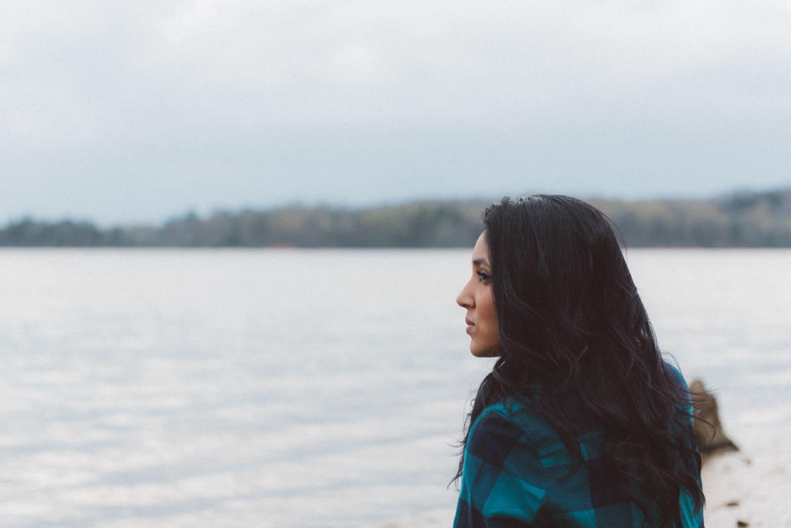 femme sérieuse avec des cheveux noirs debout près de l'eau