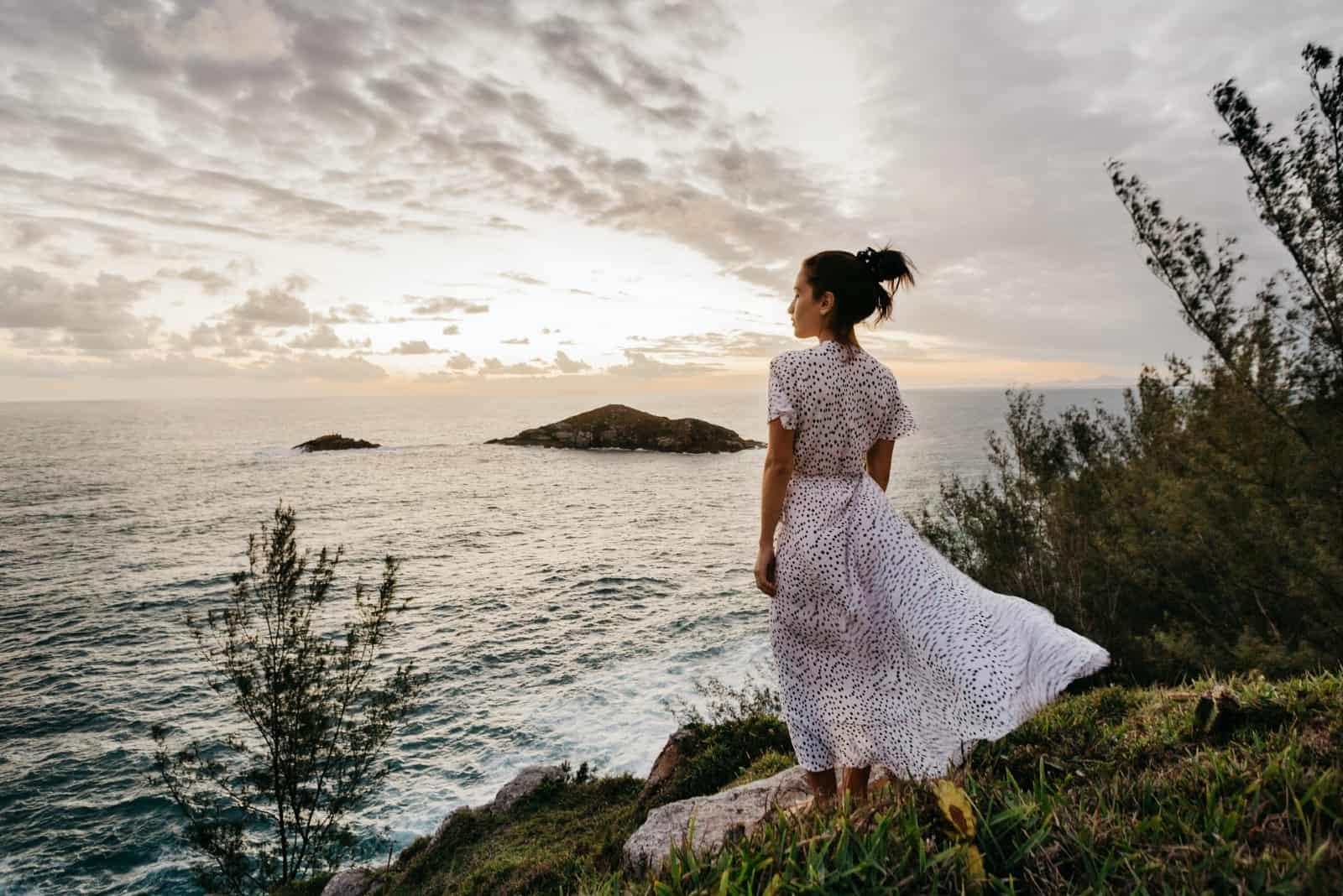 femme en robe blanche debout près de l'océan