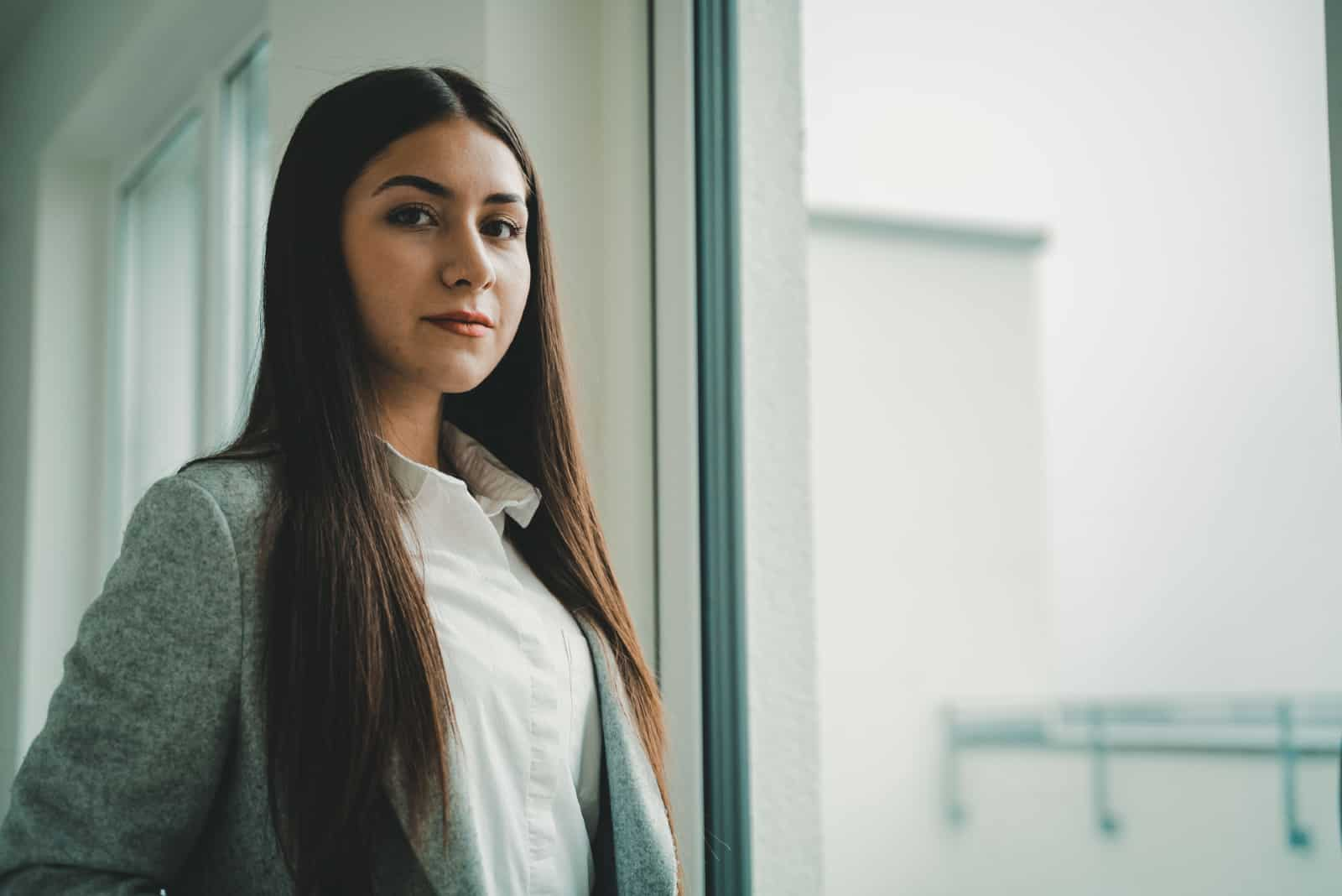 femme en blazer gris debout près d'une fenêtre