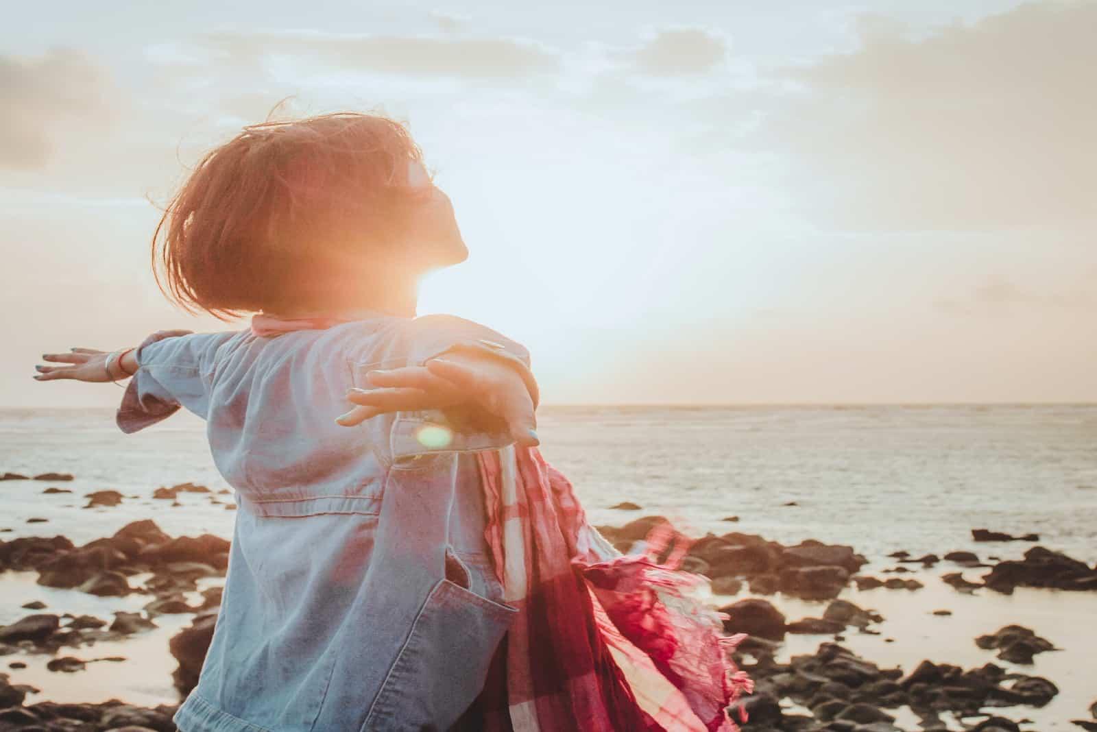 femme écartant les bras en se tenant près de la mer