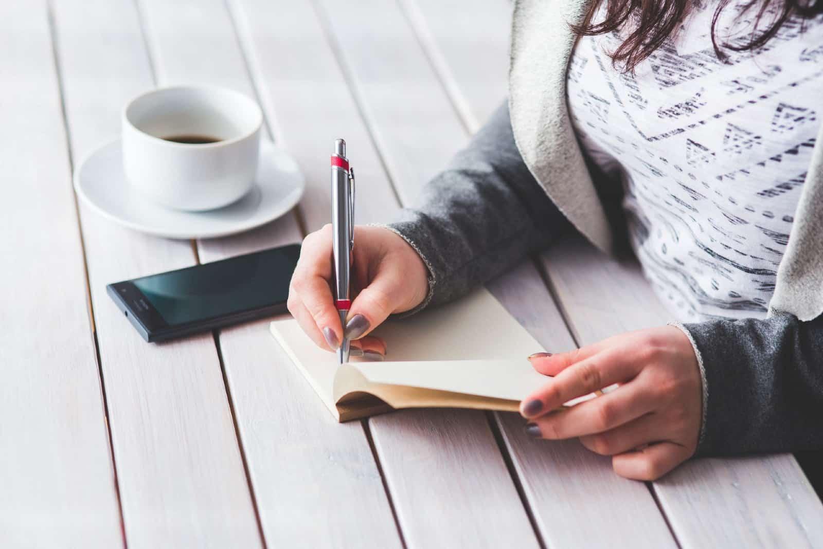 Femme écrivant sur un papier, assise à une table