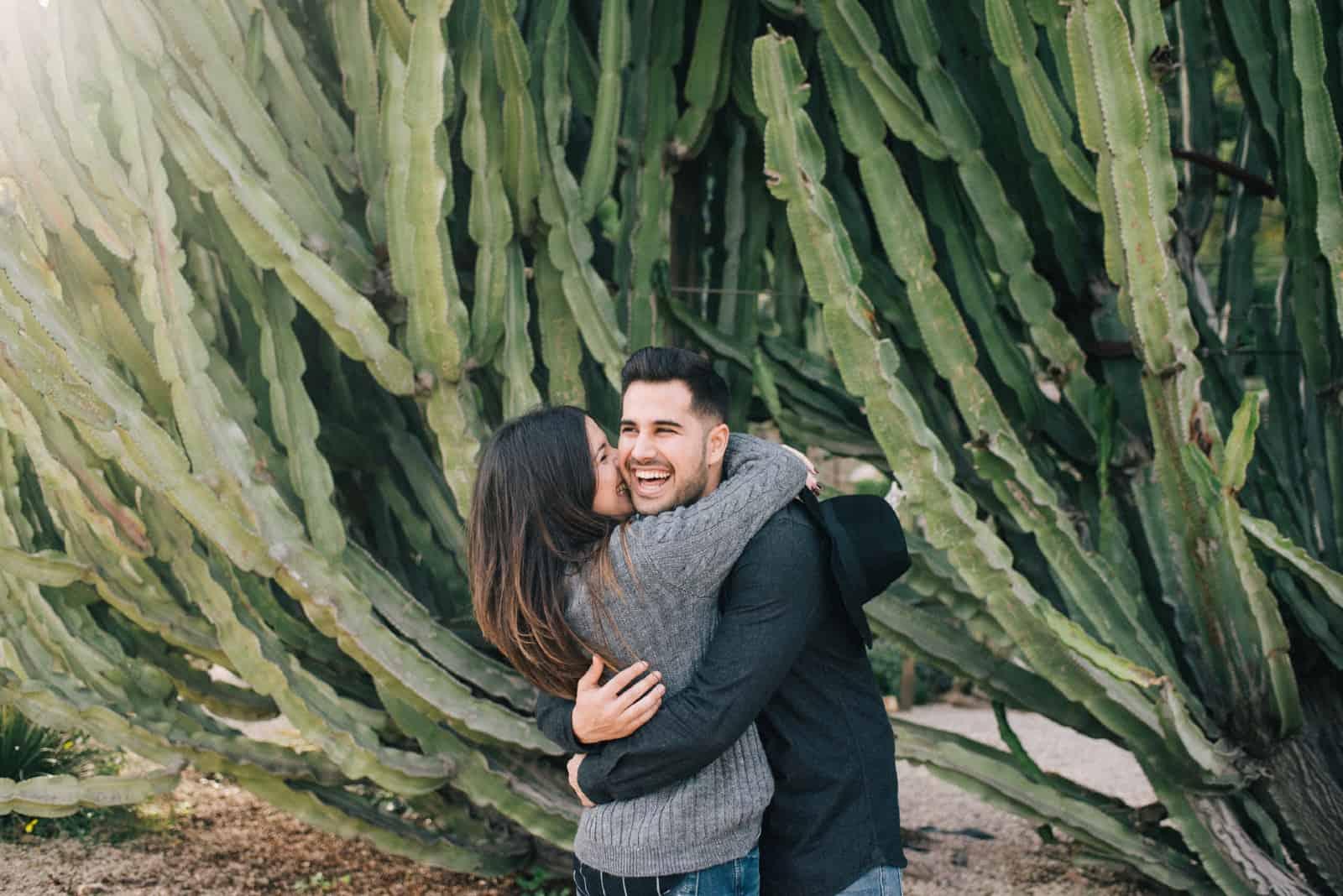 femme embrassant un homme debout près d'un cactus