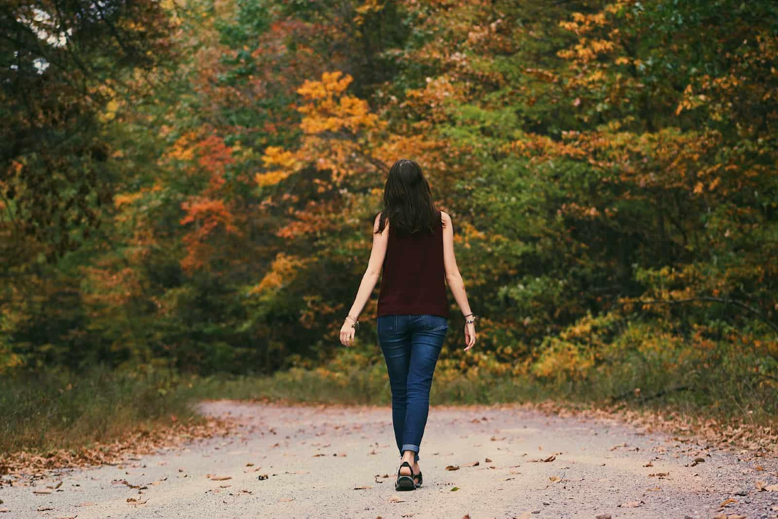 femme en blouse brune marchant dans les bois