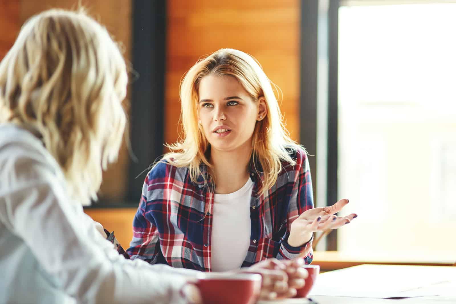 femme blonde qui parle en étant assise à une table