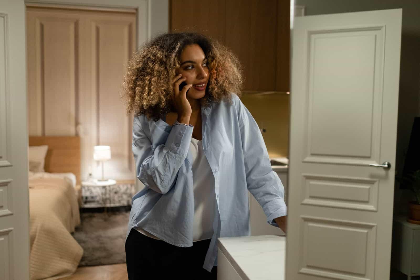 femme aux cheveux bouclés parlant sur un smartphone en intérieur