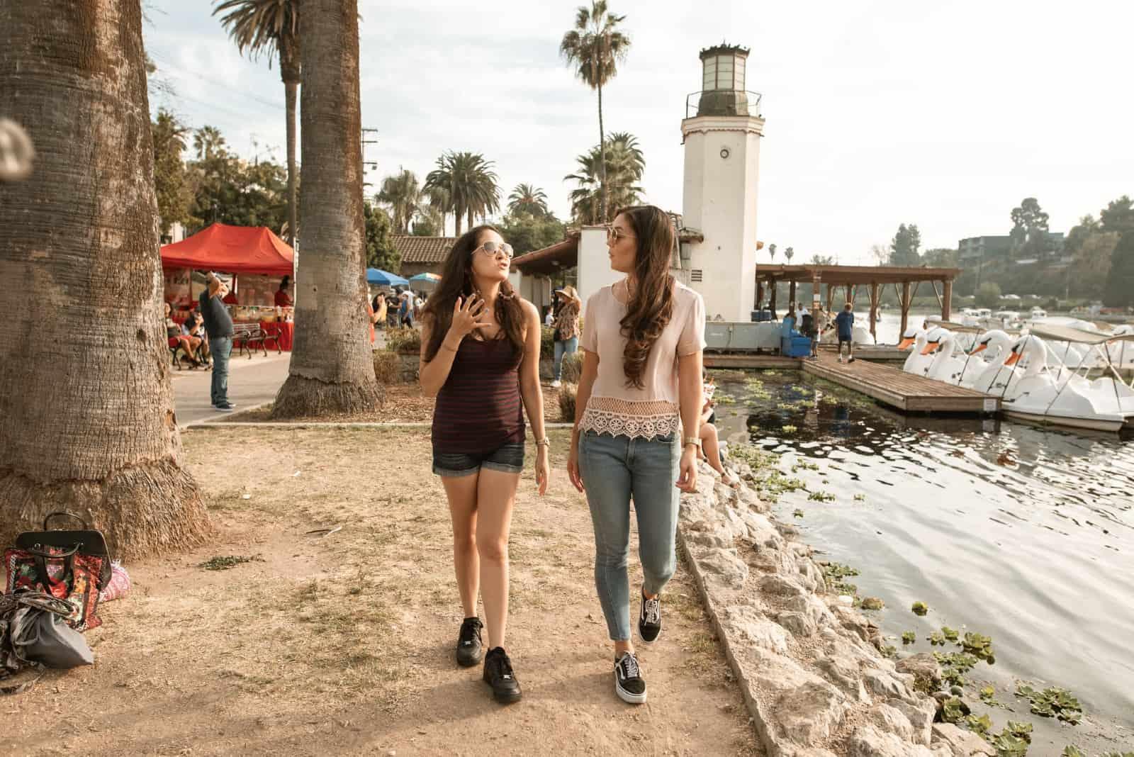 femme parlant à une femme tout en marchant près de l'eau