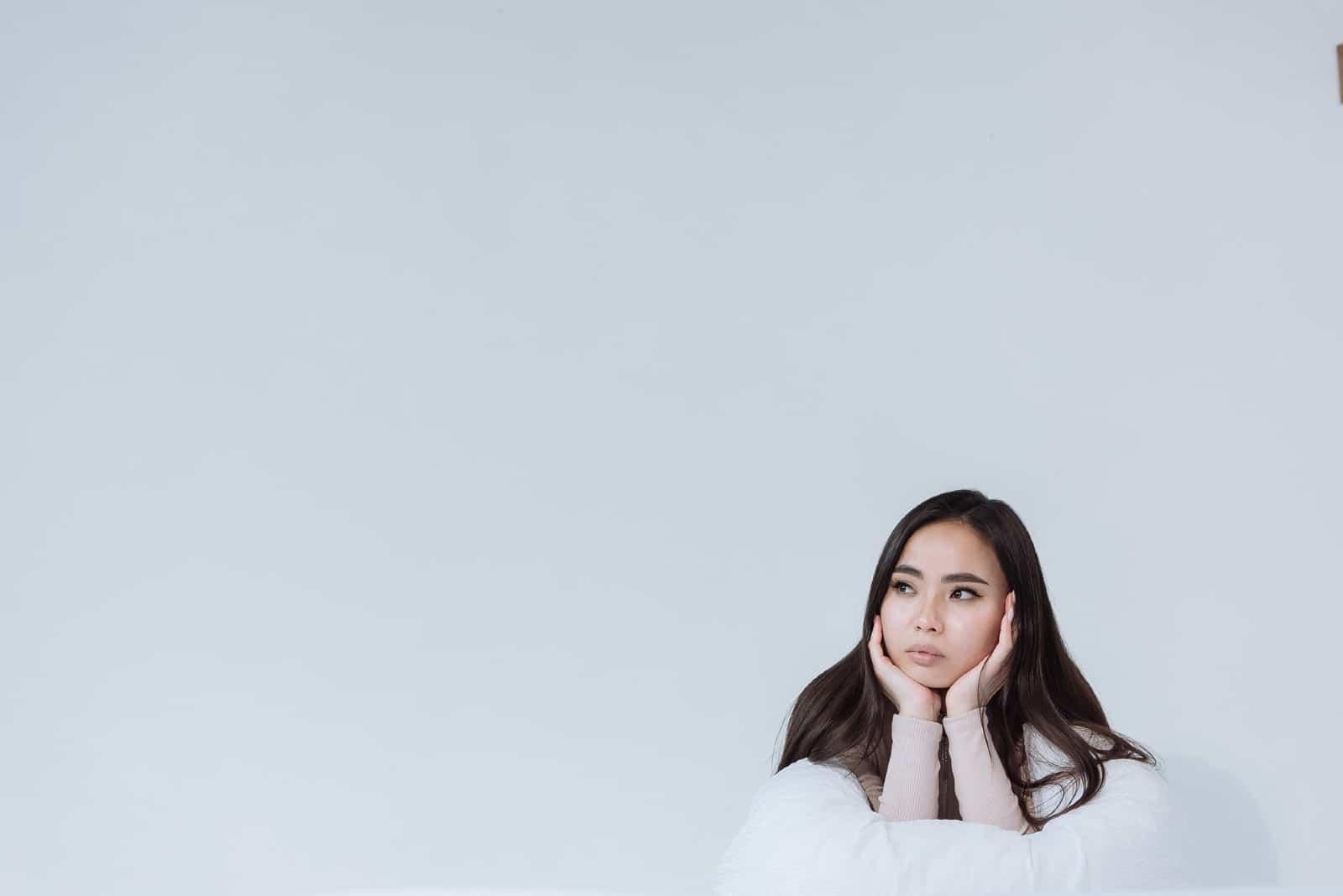 femme réfléchissant près d'un mur blanc