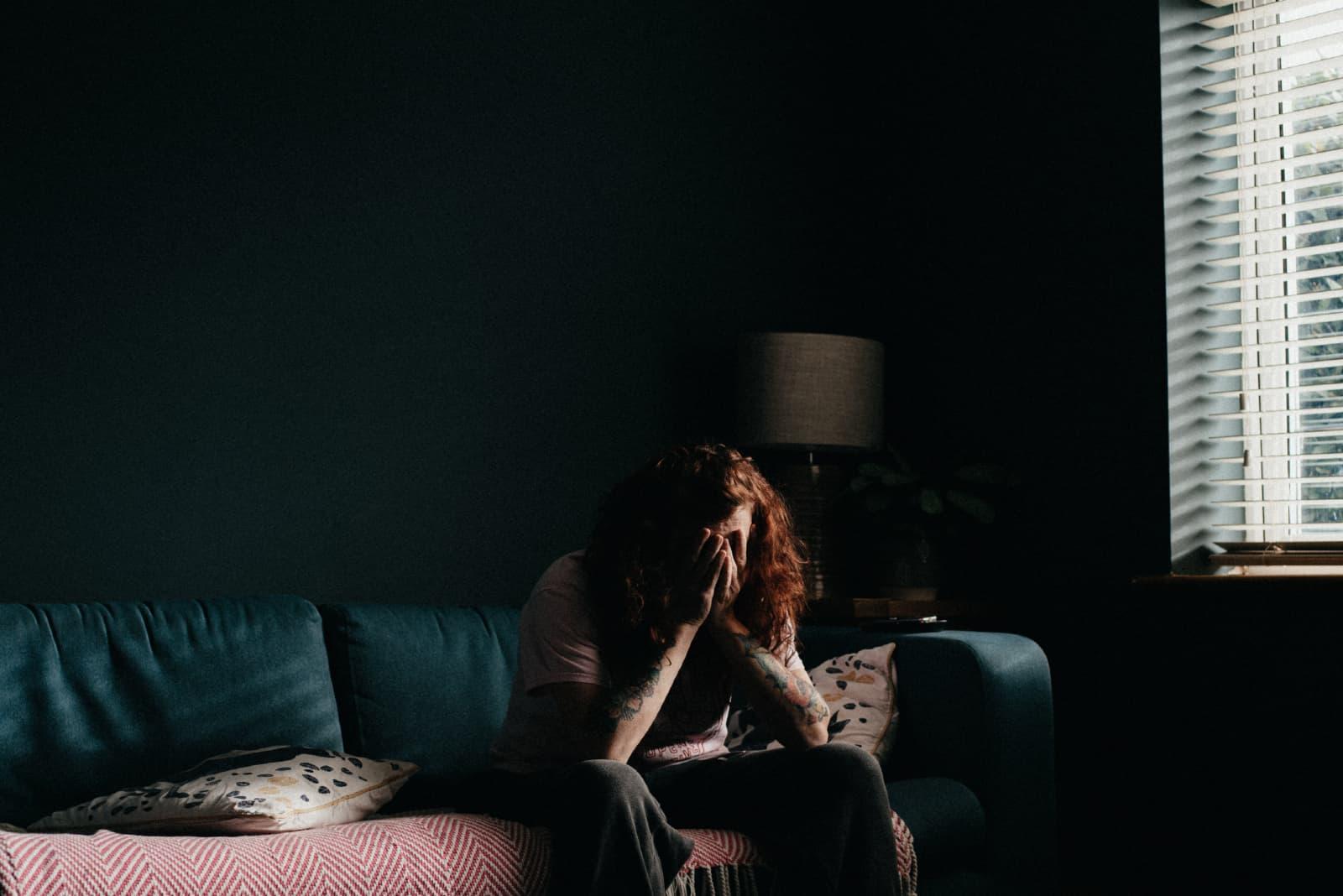 femme pleurant assise sur un canapé