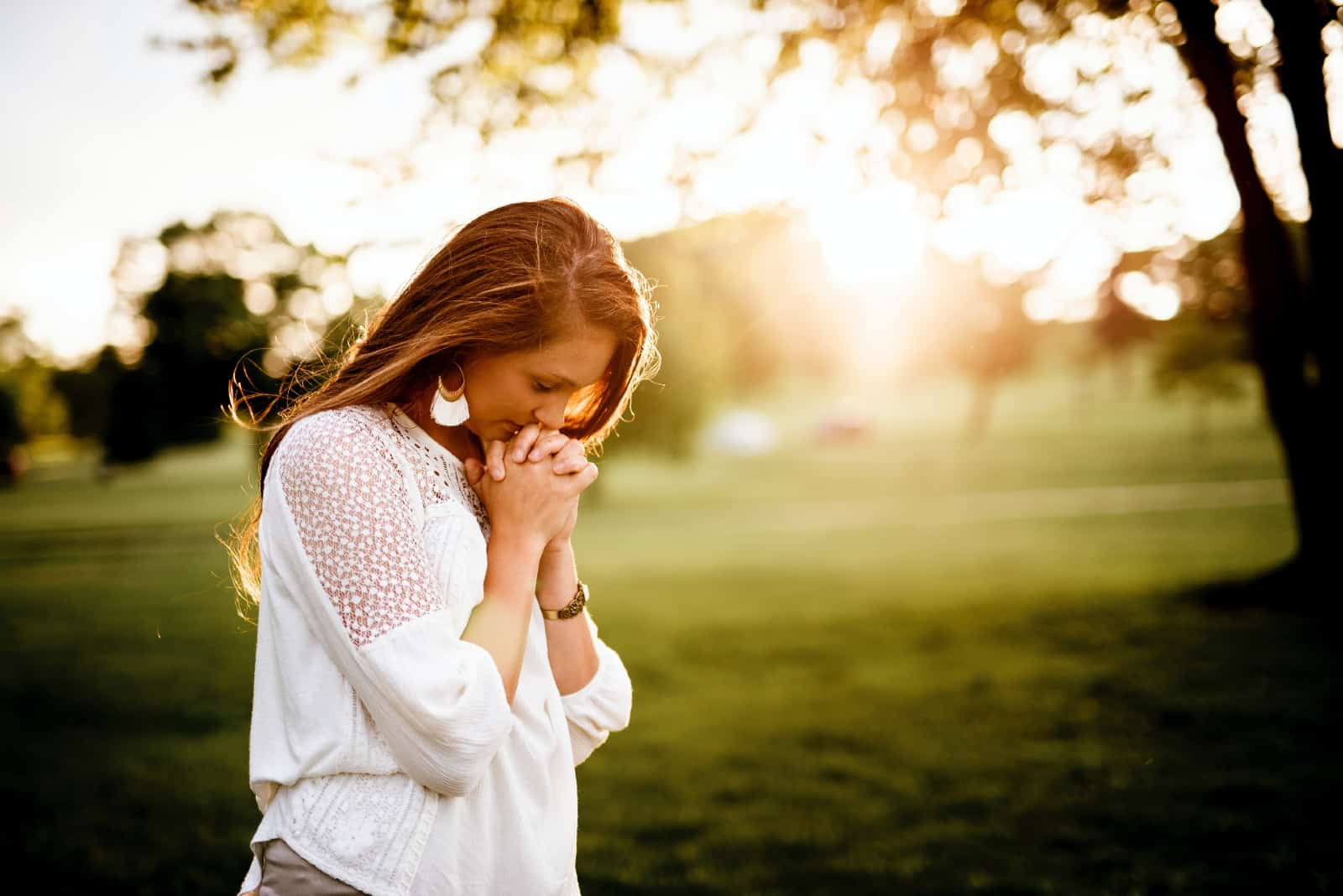 femme priant debout près d'un arbre