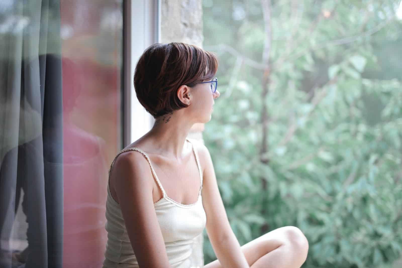 femme pensive en haut blanc regardant dehors