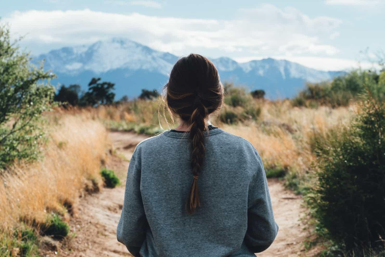 femme en sweat-shirt gris regardant la montagne