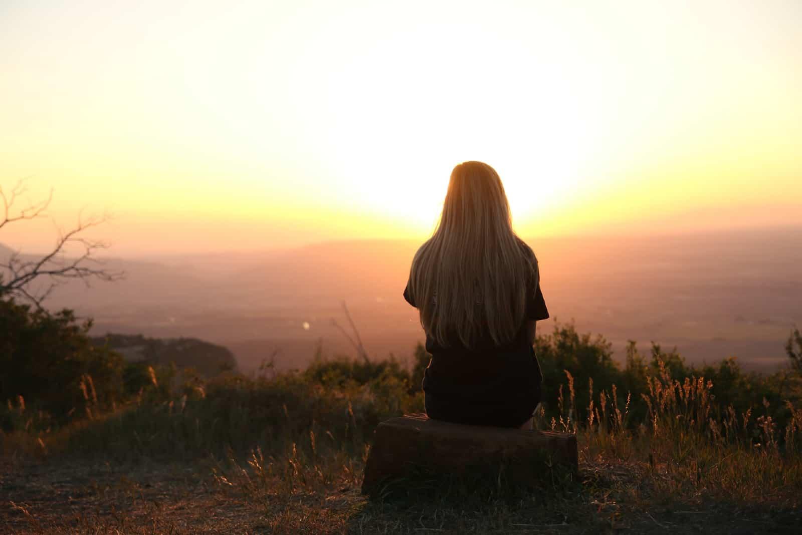 femme blonde assise sur un rocher regardant le coucher de soleil